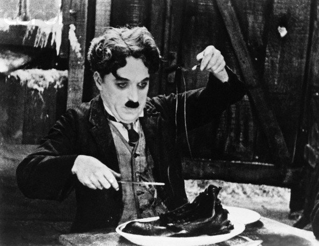 The starving Chaplin boils his shoe and makes a feast of it, The Gold Rush,1925