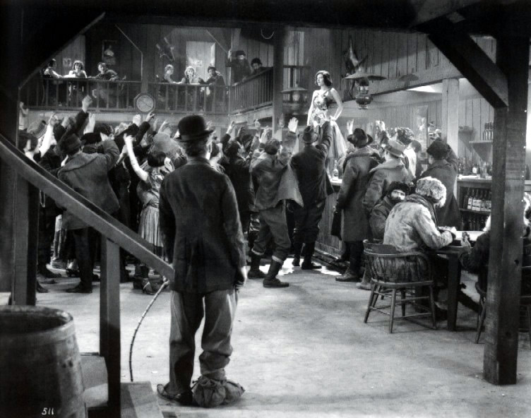 Klondike Saloon scene. Chaplin puts the camera below eye level, silhouetting his own figure so that both he and Georgia ( Georgia Hale ) stand apart.