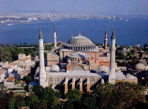 The original exterior of the Hagia Sophia is buried today under a lumpish mass of buttresses, minarets, and other accretions.