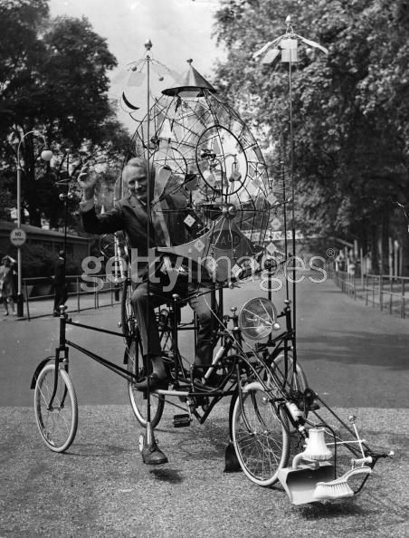 """''Cartoonist and inventor Rowland Emett rides his """"lunacycle"""" invention. The lunacycle's """"scientific refinements"""" allow it to be soft landed on the moon. Its features include a cat for companionship and for catching moon mice, and a fly-swatter rig for keeping meteorites at bay and shielding the instruments from the rays of the sun. London, England, June 11, 1970.''"""