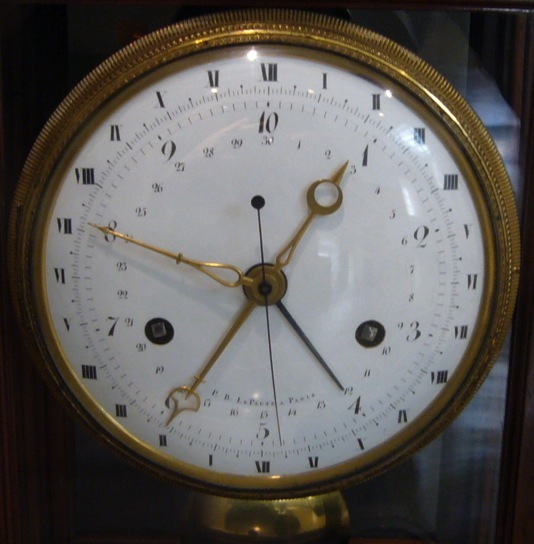 ''The single long hand with a circle at one end and a point at the other probably shows the hours in both old and new systems. One end points to the decimal time, with 10 (0) being midnight, and 5 being midday, the other end to the equivalent old-style time. Presumably, therefore, old-style midnight (XII) is at the bottom of the dial, so that the other end can point to 10 (0). 1 o'clock (decimal) is about 02:20 old style, and the position of the hour hand in this photograph suggests that the time is 0.90 (d), or 02:10 old style.''