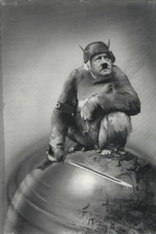 """John Heatfield:1943  This piece refers to a remark made by Galileo when he was forced to deny his belief that the Earth moved around the sun. Upon his release from the Inquisition, he stamped the Earth with his foot and said, """"And yet it moves."""" This image shows that despite Hitler's terror, the world survived."""