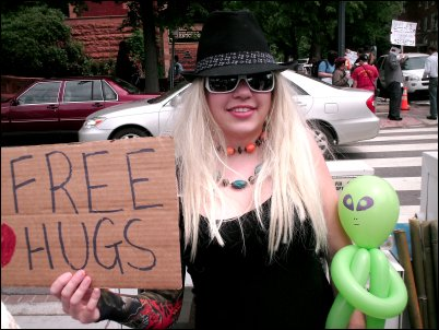 """Scientology demo D.C. ''Posing with a """"Free Hugs"""" sign and our little friend... ''"""